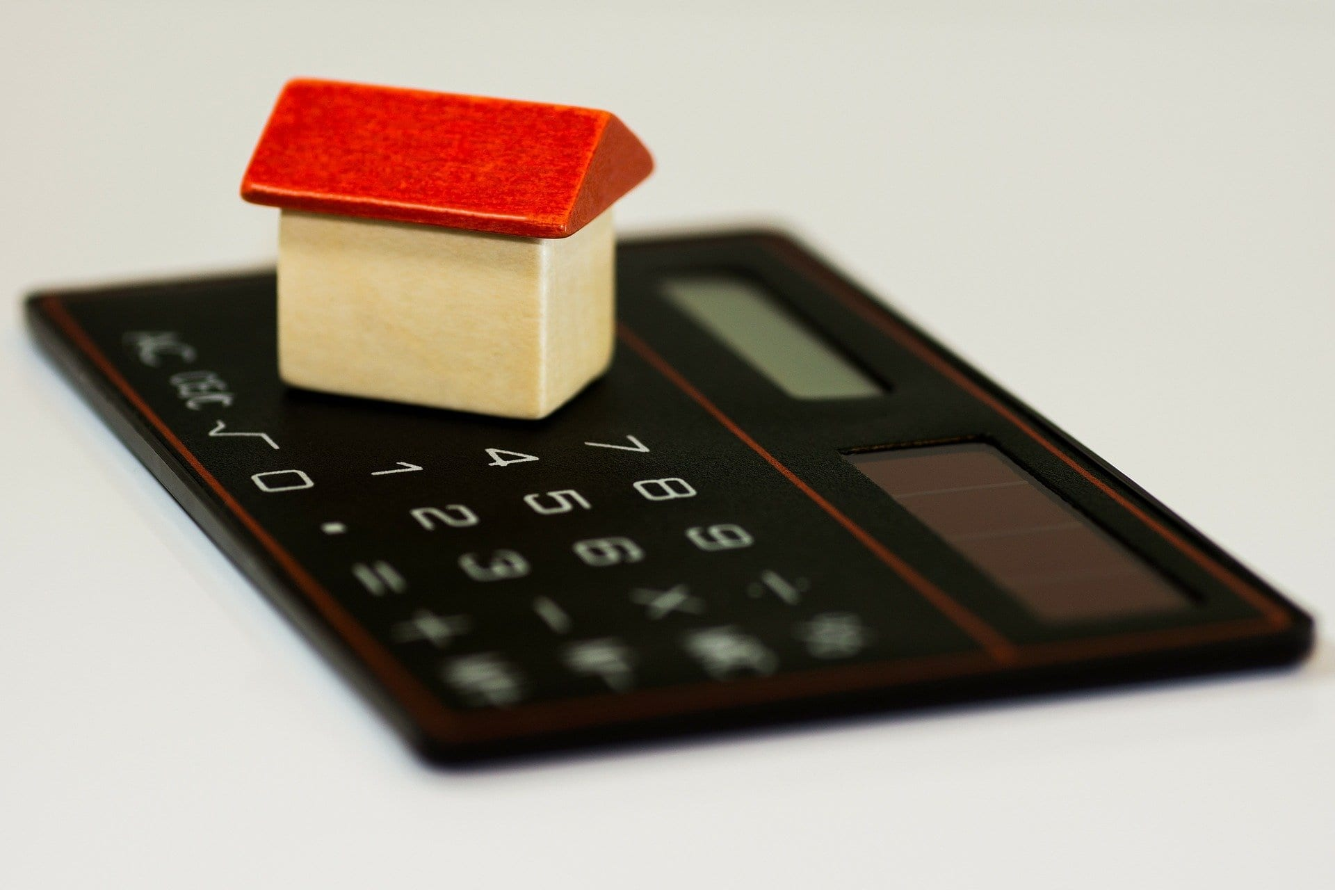 Calculator and small house representing debt restructuring