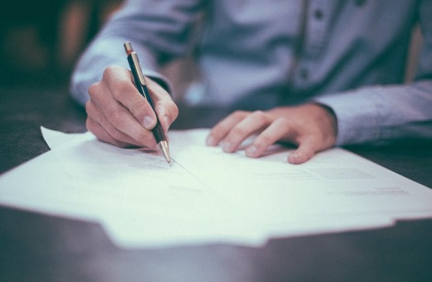 businessman signing hotel loan papers